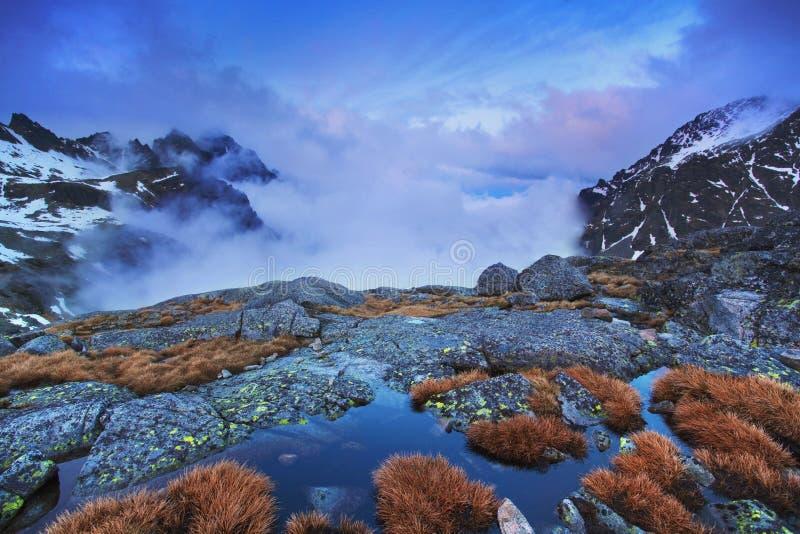 Enorma berg med perfekt himmel i solig dag Frostad dimma som t?cker dalen i solbelyst under soluppg?ng alpin royaltyfria bilder