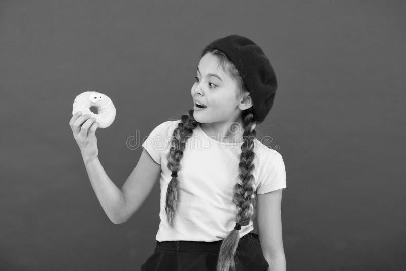 Enorma fans f?r ungar av bakade donuts Om?jligt att motst? den nya gjorda munken Glasad gullig munk f?r flicka h?ll i den r?da ha fotografering för bildbyråer