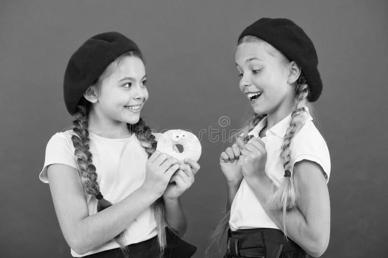 Enorma fans f?r ungar av bakade donuts S?t munk f?r aktie Flickor i baskerhattar rymmer r?d bakgrund f?r den glasade munken Sk?mt arkivfoto
