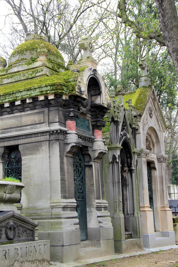 Enorma gravstenar som täckas i tung mossa, uppsättning längs banor i Pere LaChaise Cemetery, Paris, Frankrike, 2016 royaltyfri fotografi
