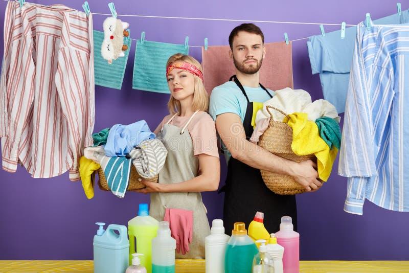 Enorma unga par som hemma gör tvätterit royaltyfri bild
