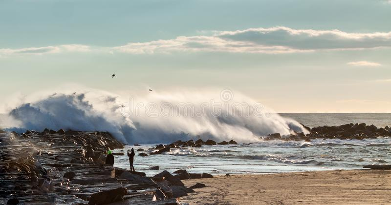 Enorma vågor som bryter över vågbrytaren royaltyfria foton