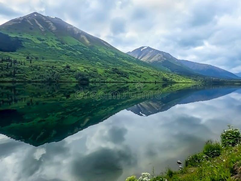 Enorme Berge reflektieren sich im Wasser in Alaska stockbild