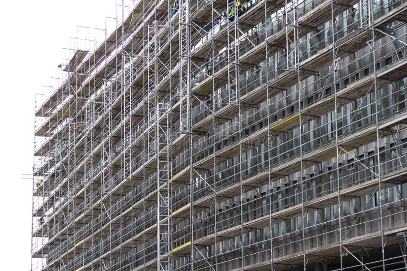 Enorme Gebäudefassade mit Baugerüst, Baustelle stockbilder