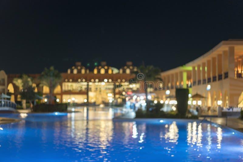 Enorme hotel noturno com piscina Blurry imagem de stock
