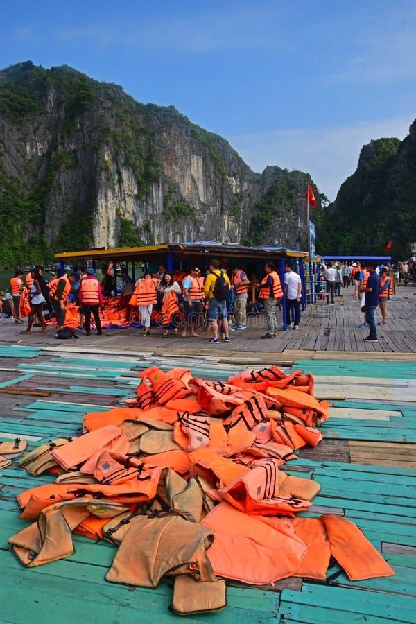 Enorme Menge Touristen an den Übergabestellen vom Kram-Schiff zum kleinen rudernden Bambusboot in Halong-Bucht für Tagesreise lizenzfreie stockbilder