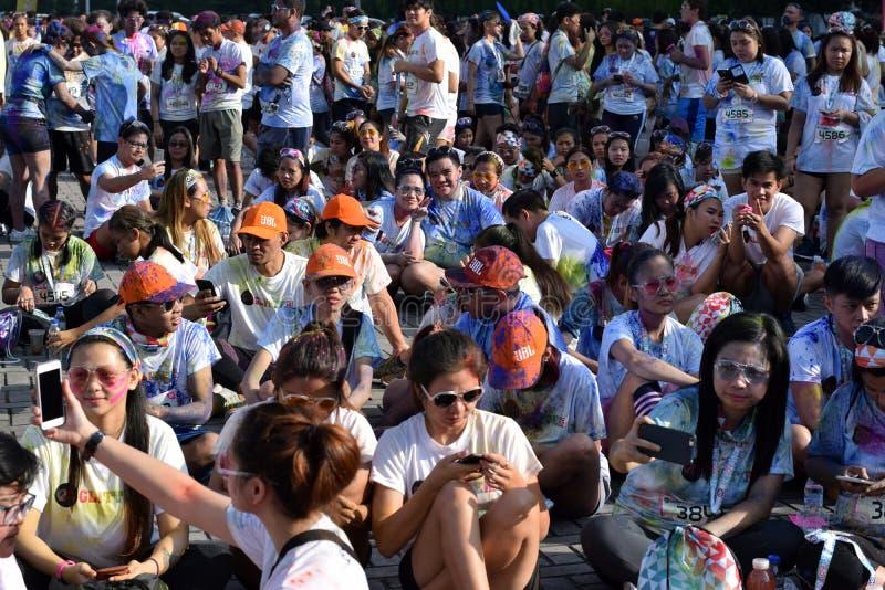 Enorme Menge von jungen Leuten treten an Farb-Manila-Funkeln zusammen, das auf Stadtplatz laufen gelassen wird Allgemeines Ereign lizenzfreies stockbild