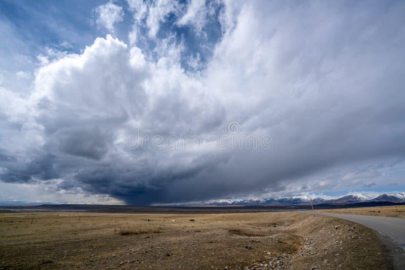 Enorme Regen-Wolken über der Straße, zu schneien Berge auf Ebene mit blauem Himmel und weißen Wolken stockbild