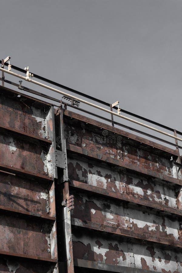 Enorme weggelaufene Stahlwand mit Rohren entlang der Spitze, grauer Himmel stockfoto