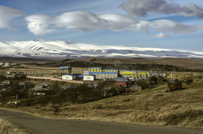 Enorme Wolken im Winter auf einem blauen sonnigen Himmel über einem Bergdorf mit Unternehmen in den Tiefländern von Schnee-mit ei lizenzfreie stockbilder