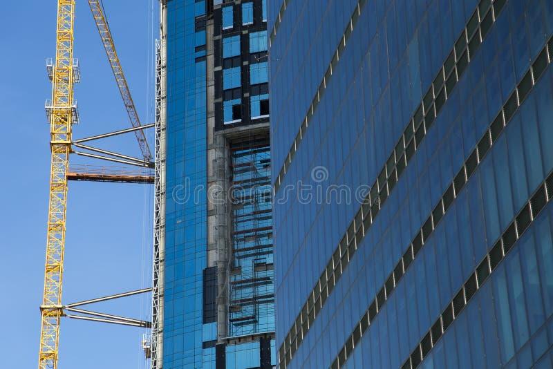 Enormer Kran, der nahe Bau eines Wolkenkratzers gegen blauen Himmel in Istanbul steigt lizenzfreie stockfotografie