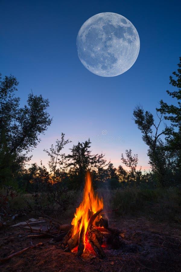 Enormer Mond auf dem nächtlichen Himmel über dem Lagerfeuer lizenzfreie stockfotos