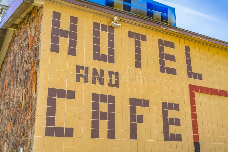 Enormes Hotel- und Cafézeichen auf der Außenwand eines Gebäudes mit Lichtern im Freien lizenzfreies stockfoto