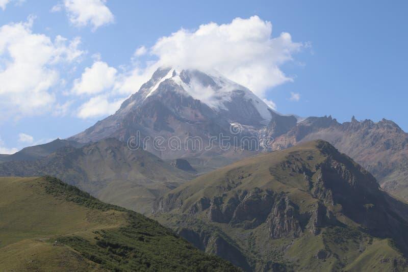 Enormt berg Kazbegi och vita moln upp över arkivbild