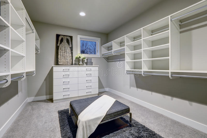 Enormt gå-i garderoben med hyllor, enheter och grå färgbänken arkivfoton