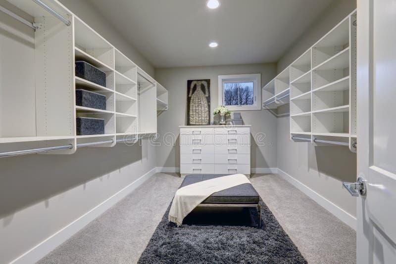 Enormt gå-i garderoben med hyllor, enheter och grå färgbänken royaltyfria bilder