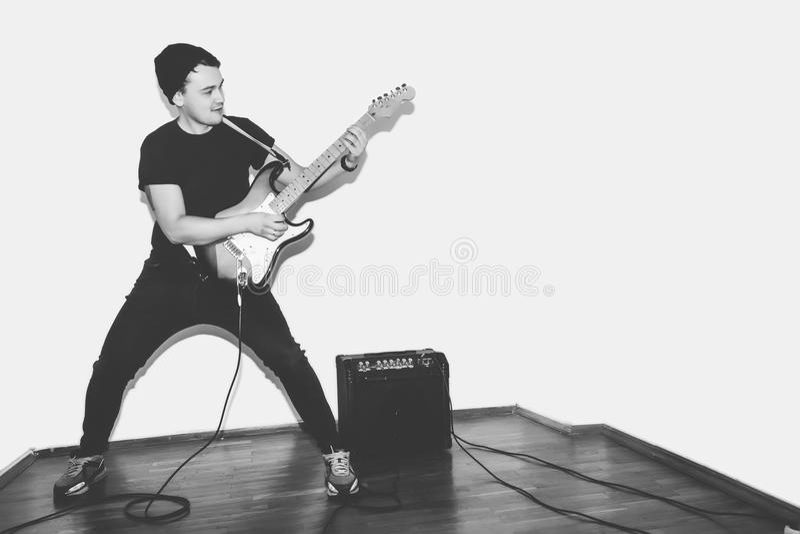 Enormt galet mode som den unga musikern vaggar gitarrspelaren, hoppar med passion i studio Stilfull stenig emotionell man _ royaltyfri foto