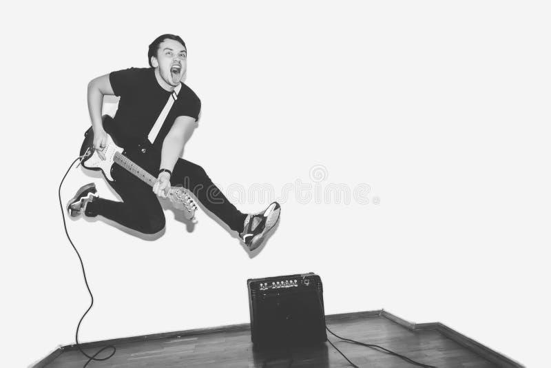Enormt galet mode som den unga musikern vaggar gitarrspelaren, hoppar med passion i studio Stilfull stenig emotionell man _ arkivfoto