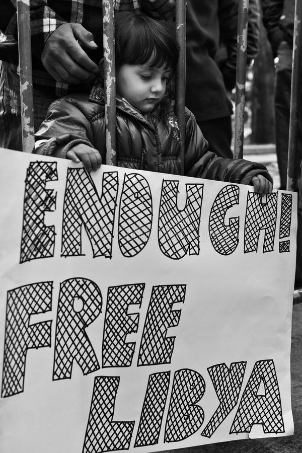 Enough!. ATTARD, MALTA - FEB 22 - A Libyan anti-Gaddafi child holds a placard during a protest in front of the Libyan Embassy in Malta on 22nd February 2011. The royalty free stock photos