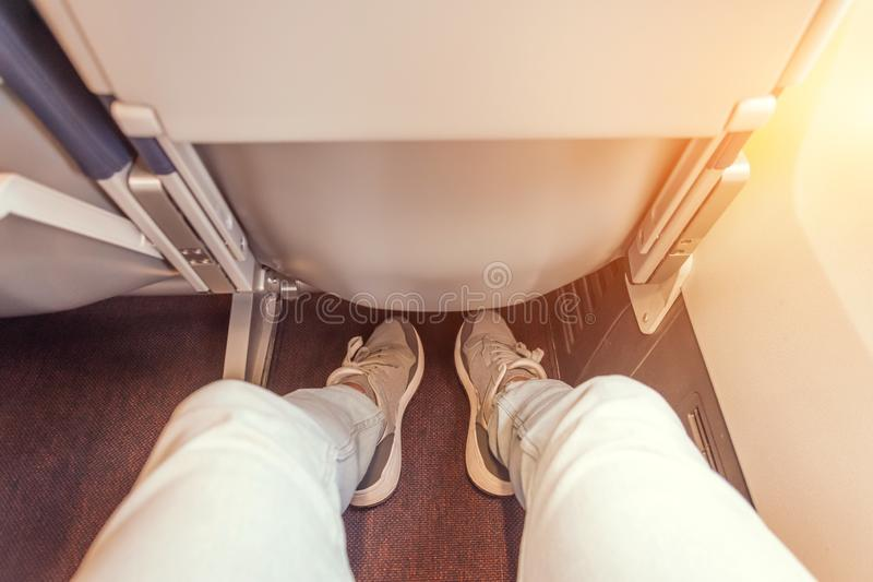 Enough legroom between the seats in the passenger plane, the view of the men`s legs. Comfortable flight free space plus stock photo