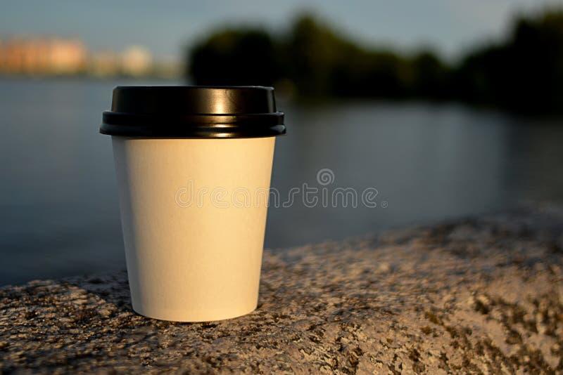 Enplast- kopp för te och kaffe är på en stenvägg på invallningen i aftonen som väntar, royaltyfria bilder