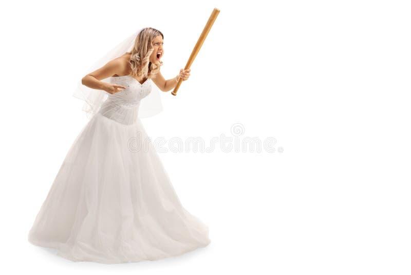 Enraged bride holding a baseball bat. Full length portrait of an enraged bride threatening someone with baseball bat isolated on white background royalty free stock photography