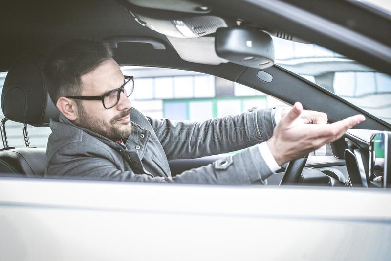 Watch out. Enraged male driver shouts and gestures threateningly royalty free stock image