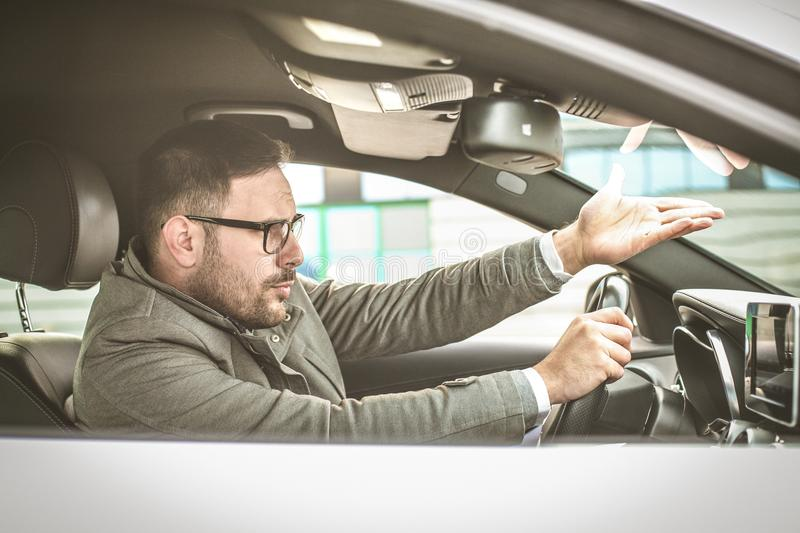 What you doing. Enraged male driver shouts and gestures threateningly stock photography