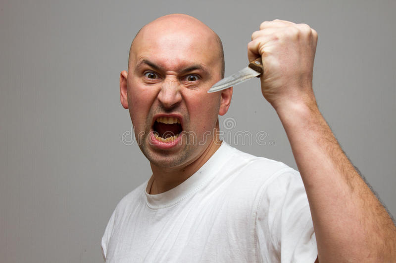 Enraged man with a knife in a murderous rage. Enraged man with a knife aggressive, frustrated portrait man, holding his fist up on black background stock photo