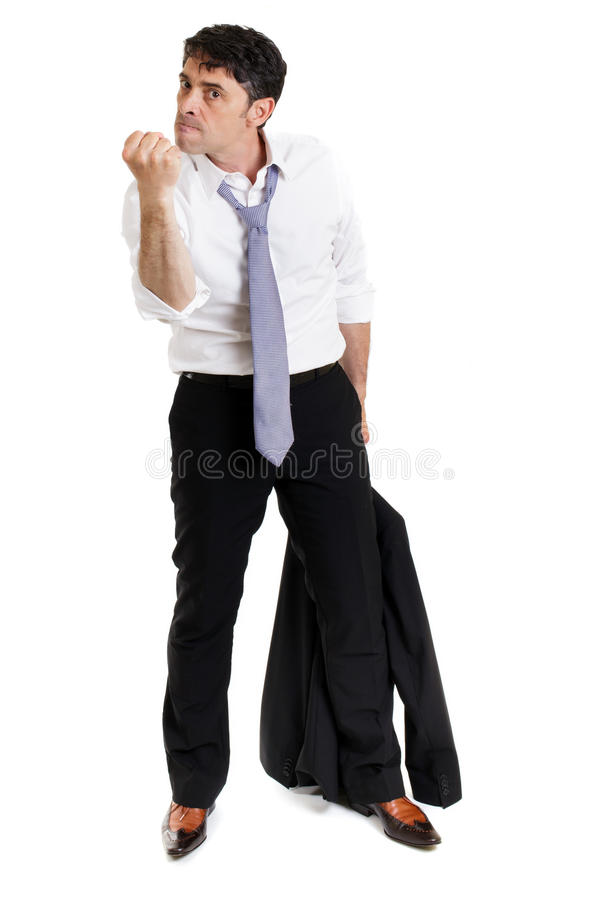 Enraged man making a threatening. Enraged business man with his suit jacket in his hand making a threatening gesture with his fist and giving a belligerent look royalty free stock photography