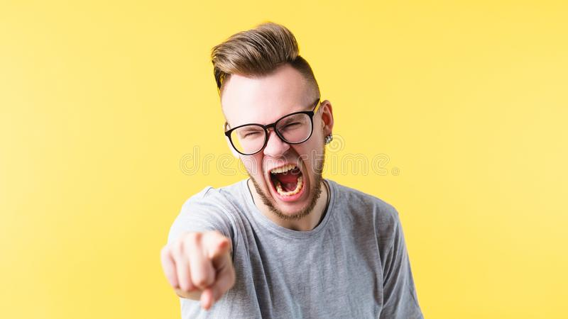 Enraged man screaming pointing mouth open anger. Enraged young man bearded hipster screaming pointing at you. Mouth wide open. Anger irritation bad temper royalty free stock photos