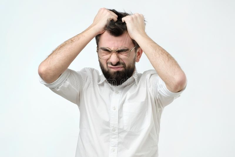 Enraged young businessman pulling his hair out for exasperation, having a burnout at work. Screaming for frustration and stress royalty free stock photos