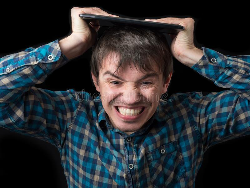 The enraged young man breaks the tablet on his head. Bad device. Disappointment and anger.  stock photography