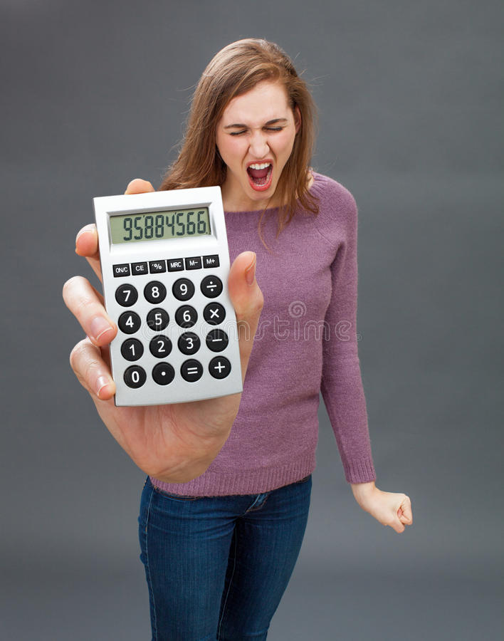 Enraged young woman screaming against financial economy on oversized calculator. Enraged young woman standing with a nervous fist, screaming against financial stock images