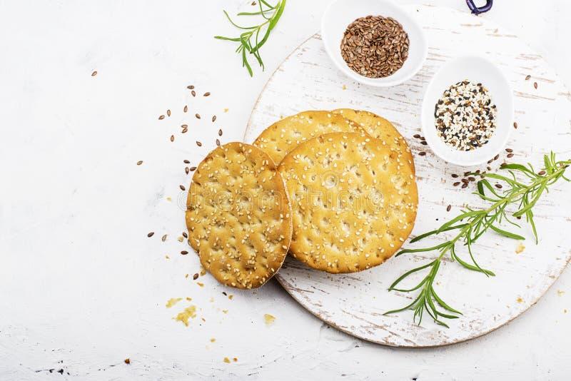 Enrarezca los panes curruscantes del grano para el desayuno con las semillas de lino y las semillas de sésamo en un fondo ligero  foto de archivo