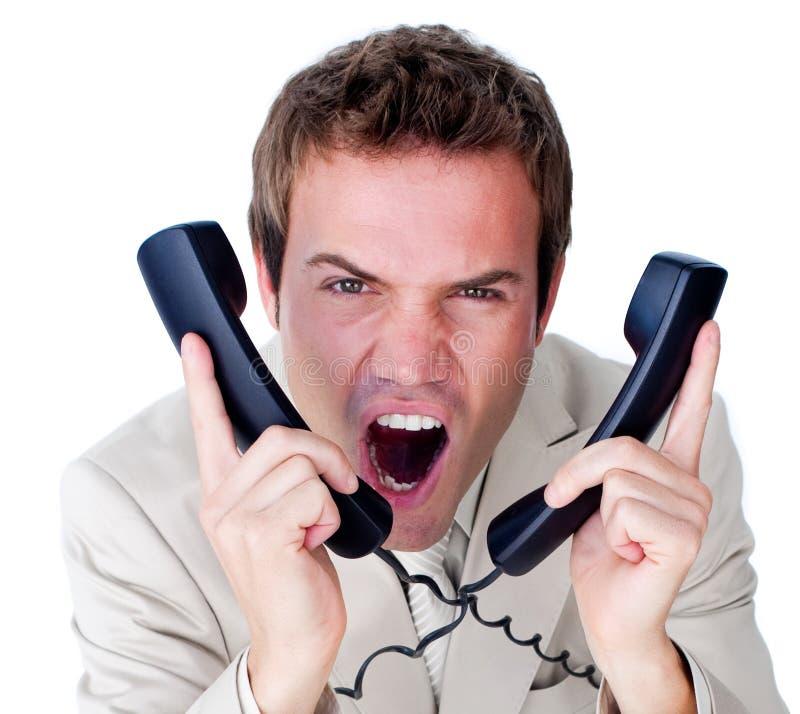 Enredo furioso del hombre de negocios para arriba en alambres del teléfono imagen de archivo