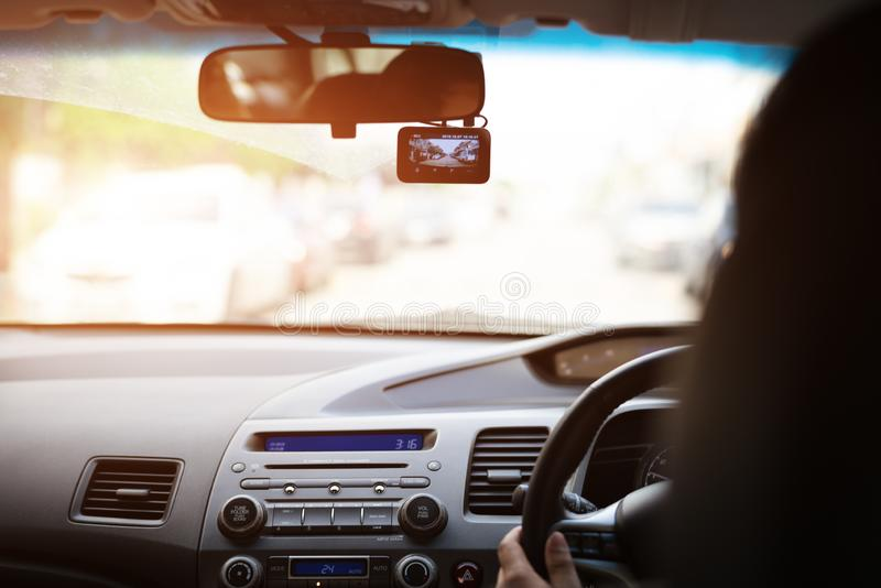 Enregistreur avant de voiture de caméra, eoman conduisant une voiture avec le magnétoscope à côté d'un miroir de vue arrière image stock