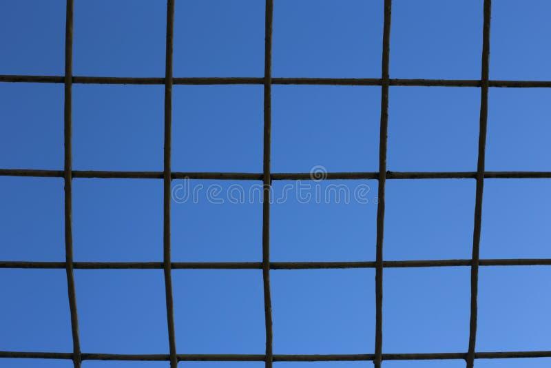 Enrejado contra el cielo azul foto de archivo