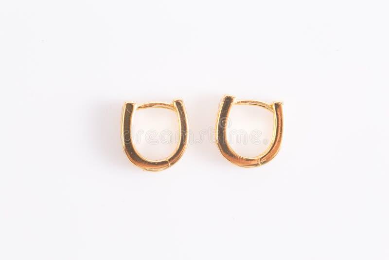 Enrelaçamentos Ouro Hoop Earrings com diamantes em fundo branco fotografia de stock