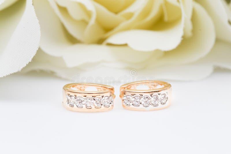Enrelaçamentos Ouro Hoop Earrings com diamantes em fundo branco foto de stock
