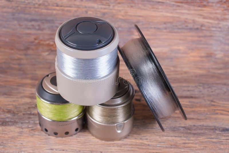 Enrole a ferida com uma linha de pesca para o carretel de giro Fundo de madeira fotografia de stock
