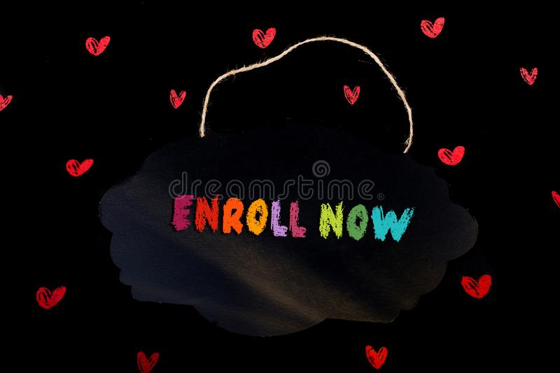 Enroll now wording written on blank sign board  in hand stock illustration
