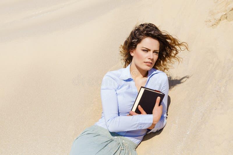 Enroulez la fille d'étudiant de cheveux détendant sur le sable photo stock