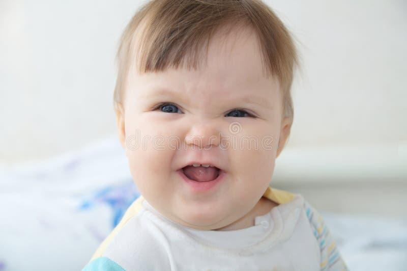 Enrugando o retrato infantil engraçado do bebê, cara de sorriso feliz da criança que expressa a emoção imagem de stock