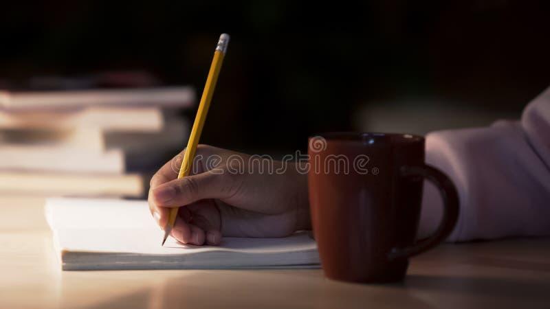 Ensaio Biracial da escrita do estudante na biblioteca, copo de chá que está na mesa, close up foto de stock royalty free