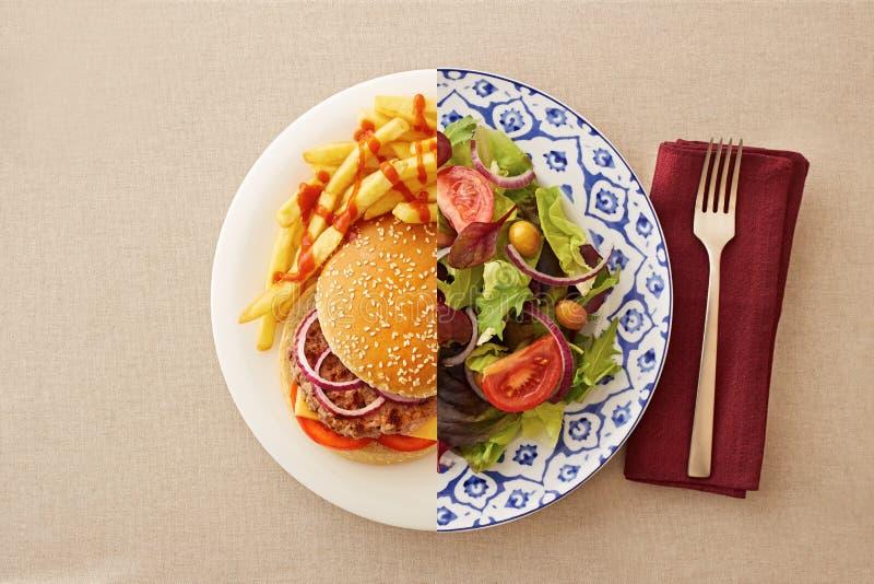 Ensalada baja en grasa contra la hamburguesa grasienta imagen de archivo libre de regalías