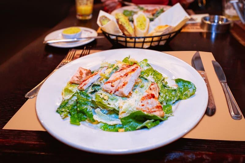 Ensalada César con el pollo y hojas verdes en la placa blanca en un restaurante foto de archivo libre de regalías