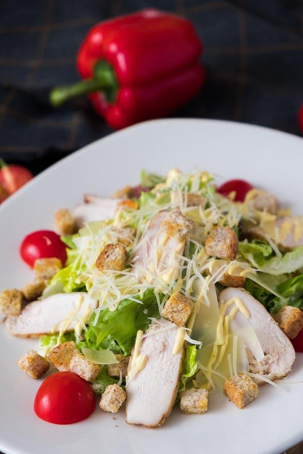 Ensalada C?sar fresca con el pollo en una placa blanca en fondo de piedra oscuro El plano pone con los ingridients para el cocine fotografía de archivo