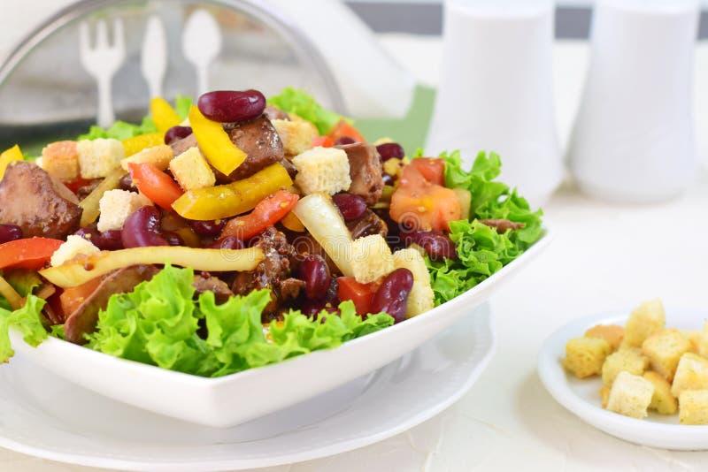 Ensalada caliente con el hígado de pollo, las habas, los tomates, la paprika dulce, los cuscurrones y la preparación balsámica imagen de archivo