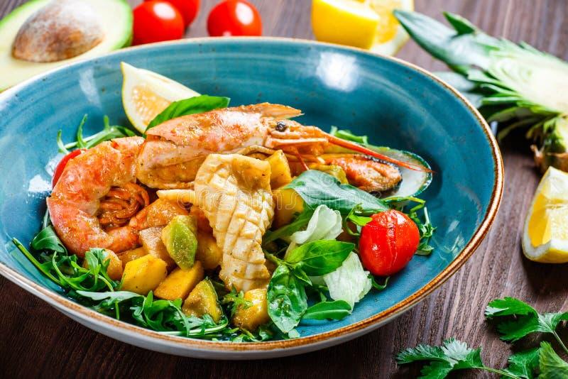 Ensalada caliente con los mariscos, langoustine, mejillones, camarones, calamar, conchas de peregrino, mango, piña, aguacate fotografía de archivo libre de regalías